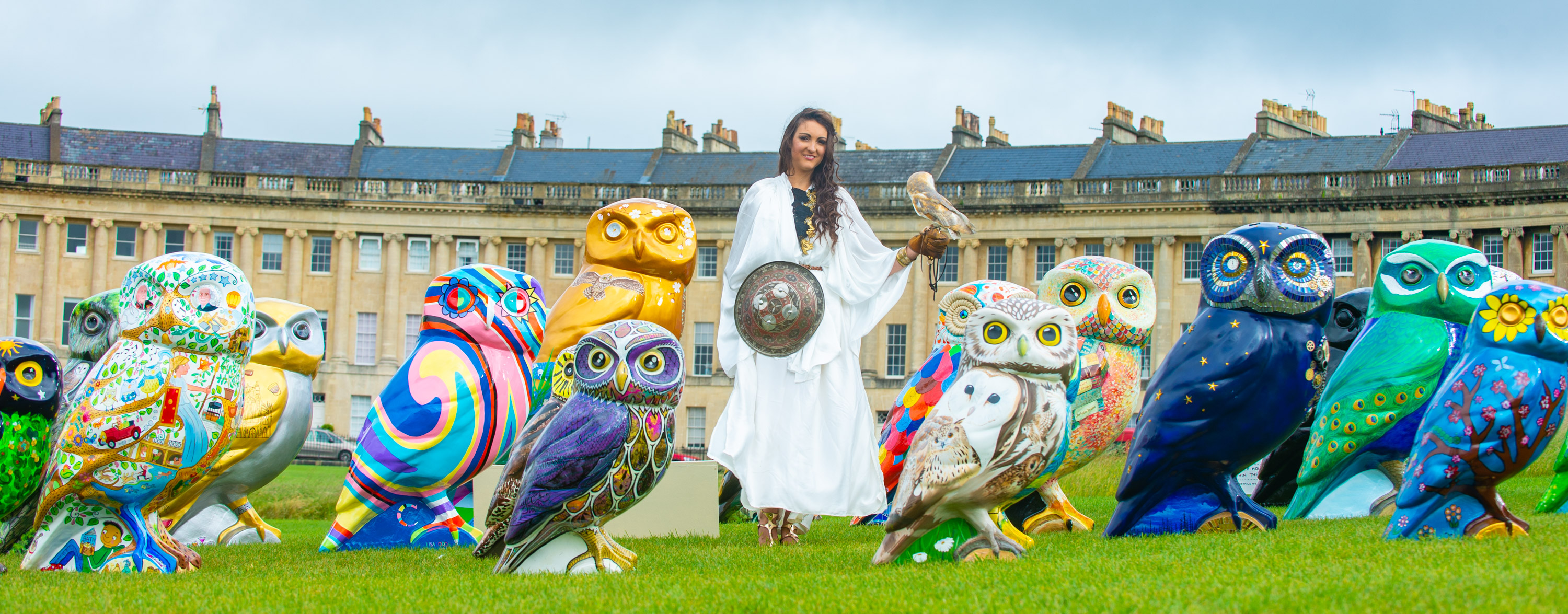 Thirty giant owl statues flock to Bath's Royal Crescent for the launch of the Minerva's Owls of Bath sculpture trail, starting on 25th June 2018. Goddess Minerva(Amelia Watt) poses with Ghost the Barn Owl alongside decorated statues from the Minerva's Owls of Bath sculpture trail, starting on 25th June 2018. Members of the public take a closer look at the decorated flock of owls ahead of the launch of the Minerva's Owls of Bath sculpture trail, starting on 25th June 2018. Tuesday 19 June 2018 PHOTO:PAUL GILLIS / paulgillisphoto.com